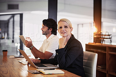 Buy stock photo Shot of a mature businesswoman using a laptop during a late night in a modern office