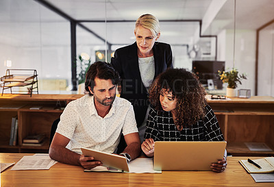 Buy stock photo Shot of a group of businesspeople using wireless devices during a late night in a modern office