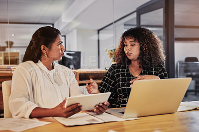 Buy stock photo Shot of two businesswomen using a digital tablet and laptop during a late night discussion in a modern office