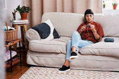 Buy stock photo Full length shot of a young woman knitting while relaxing at home