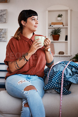 Buy stock photo Shot of a clothing designer taking a break from her work with a cup of coffee