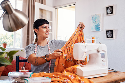 Buy stock photo Shot of a beautiful young woman working on a garment at home