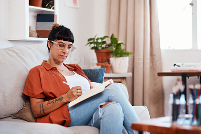 Buy stock photo Shot of an attractive young woman writing while relaxing at home