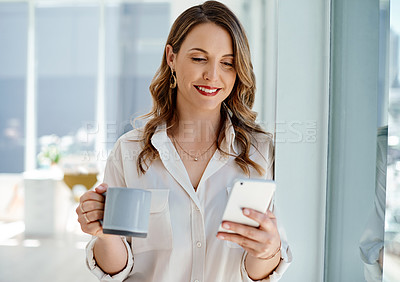 Buy stock photo Cropped shot of an attractive young businesswoman drinking coffee and using her cellphone inside of an office