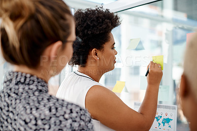 Buy stock photo Rearview shot of a group of businesswomen brainstorming with notes on a glass wall in an office