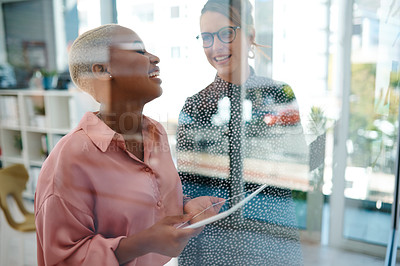 Buy stock photo Shot of two businesswomen brainstorming with notes on a glass wall in an office