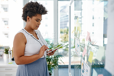 Buy stock photo Shot of a young businesswoman using a digital tablet while brainstorming with notes on a glass wall in an office