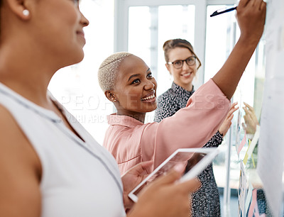 Buy stock photo Shot of a group of businesswomen brainstorming with notes on a glass wall in an office