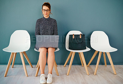Buy stock photo Studio shot of an attractive young businesswoman using a laptop while sitting in line against a grey background