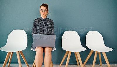 Buy stock photo Studio portrait of an attractive young businesswoman using a laptop while sitting in line against a grey background