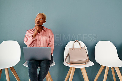 Buy stock photo Studio shot of an attractive young businesswoman looking thoughtful while using a laptop against a grey background