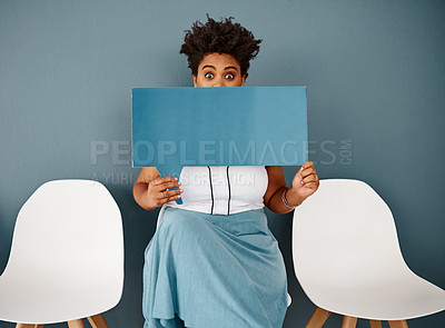 Buy stock photo Studio portrait of an attractive young businesswoman covering her face with a speech bubble while sitting against a grey background