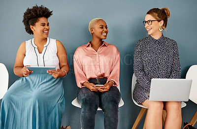 Buy stock photo Studio shot of a group of attractive young businesswomen laughing together while sitting in line against a grey background