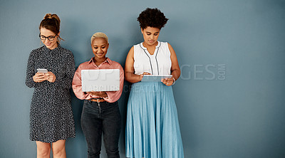 Buy stock photo Studio shot of a group of attractive young businesswomen using wireless technology while standing against a grey background