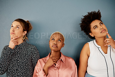 Buy stock photo Studio shot of a group of three attractive young businesswomen looking thoughtful while standing against a grey background