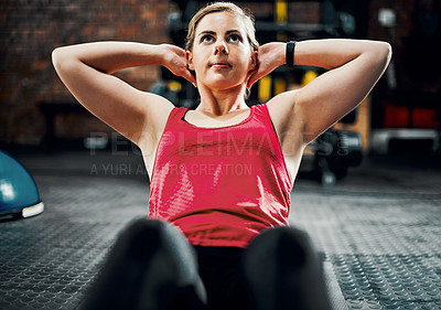 Buy stock photo Cropped shot of an attractive young female athlete doing situps in the gym