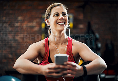 Buy stock photo Cropped shot of an attractive young female listening to music while working out in the gym