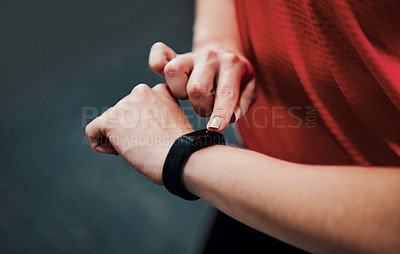 Buy stock photo Cropped shot of an unrecognizable young female athlete checking her smartwatch while working out in the gym