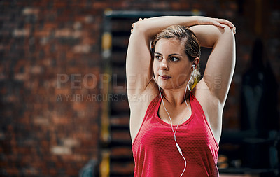 Buy stock photo Cropped shot of an attractive young female listening to music while warming up out in the gym