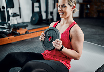 Buy stock photo High angle shot of an attractive young female athlete doing situps with a weight in the gym