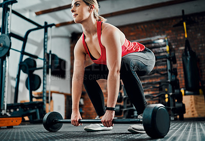 Buy stock photo Full length shot of an attractive young female athlete working out with weights in the gym