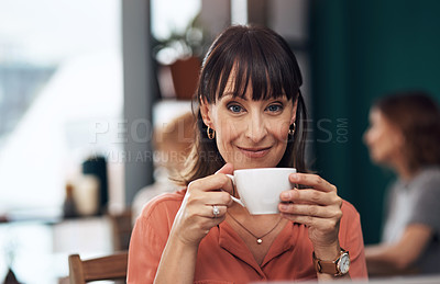 Buy stock photo Portrait of an attractive middle aged woman having a cup of coffee inside of a coffee shop during the day