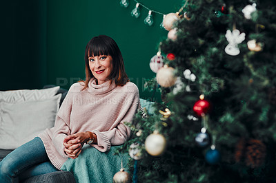 Buy stock photo Portrait of an attractive middle aged woman sitting together on a sofa next to a Christmas tree at home