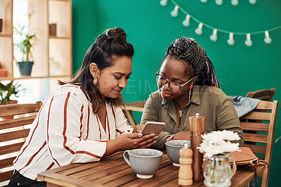 Buy stock photo Shot of two young women using a smartphone together at a cafe