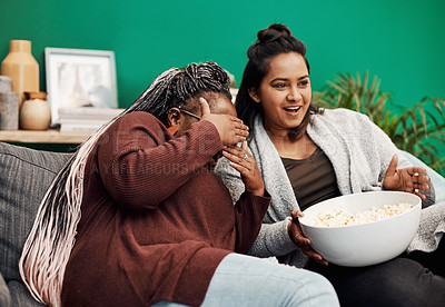 Buy stock photo Shot of two young women having popcorn and watching tv together at home