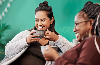 Buy stock photo Shot of two young women having coffee and chatting on the sofa at home