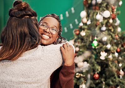 Buy stock photo Shot of two happy young women hugging each other during Christmas at home