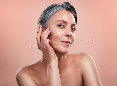 Buy stock photo Studio portrait of a beautiful mature woman posing against a peach background