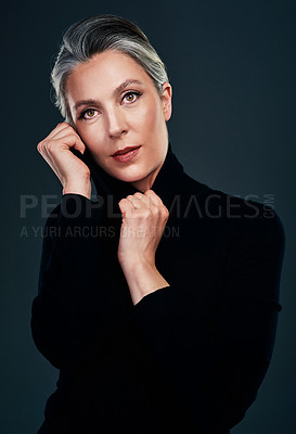 Buy stock photo Studio portrait of a beautiful mature woman posing against a dark background