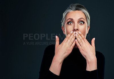 Buy stock photo Studio portrait of a beautiful mature woman looking surprised against a dark background