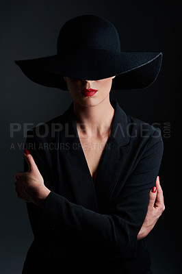 Buy stock photo Studio shot of a beautiful mature woman wearing a hat and posing against a dark background