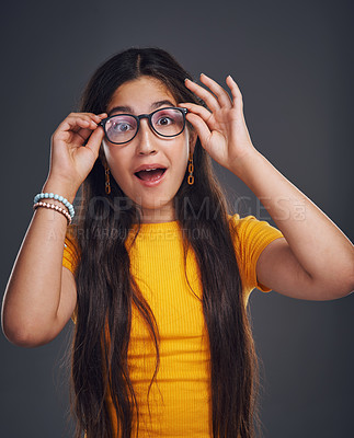 Buy stock photo Cropped portrait of an attractive teenage girl wearing glasses and feeling playful against a dark background in the studio