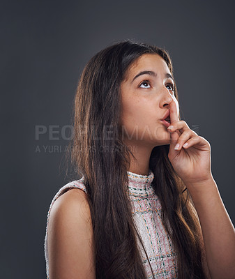 Buy stock photo Cropped shot of an attractive teenage girl standing with her finger to her lips against a dark studio background