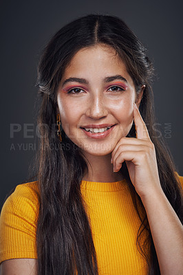 Buy stock photo Cropped portrait of an attractive teenage girl standing alone against a dark background in the studio