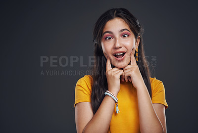 Buy stock photo Cropped shot of an attractive teenage girl standing alone against a dark studio background with her hands to her face