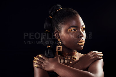 Buy stock photo Studio shot of a beautiful young woman wearing make up and jewellery against a black background