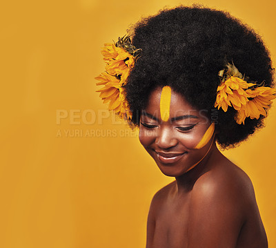 Buy stock photo Studio shot of a beautiful young woman posing topless with sunflowers in her hair against a mustard background