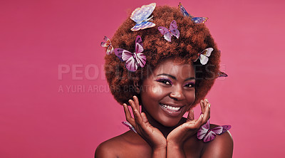 Buy stock photo Studio portrait of a beautiful young woman smiling while posing with butterflies in her hair against a purple background