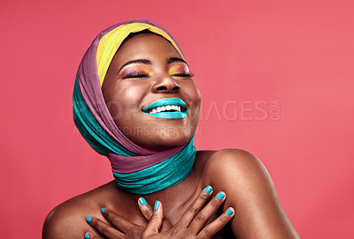 Buy stock photo Studio shot of a beautiful young woman smiling while wearing a head wrap and make up against a pink background