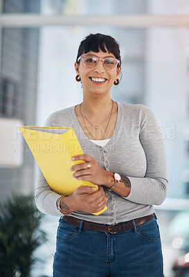 Buy stock photo Cropped portrait of an attractive young businesswoman standing alone and holding files in her office