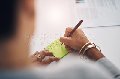 Buy stock photo Cropped shot of an unrecognizable businesswoman sitting alone in her office and writing on a post-it