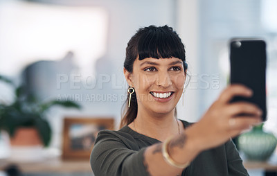 Buy stock photo Cropped shot of an attractive young businesswoman sitting alone in her office and using her cellphone to take a selfie