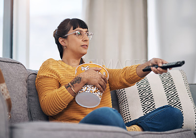 Buy stock photo Cropped shot of an attractive young woman sitting in her living room and watching a movie during a day off