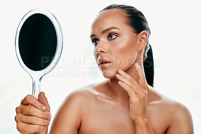 Buy stock photo Studio shot of a beautiful young woman looking into a handheld mirror