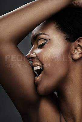 Buy stock photo Shot of a beautiful young woman biting into her arm