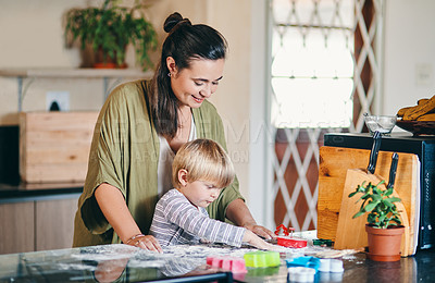 Buy stock photo Shot of an adorable little boy baking with his mother at home